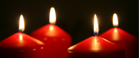 four candle flames shining in darkness